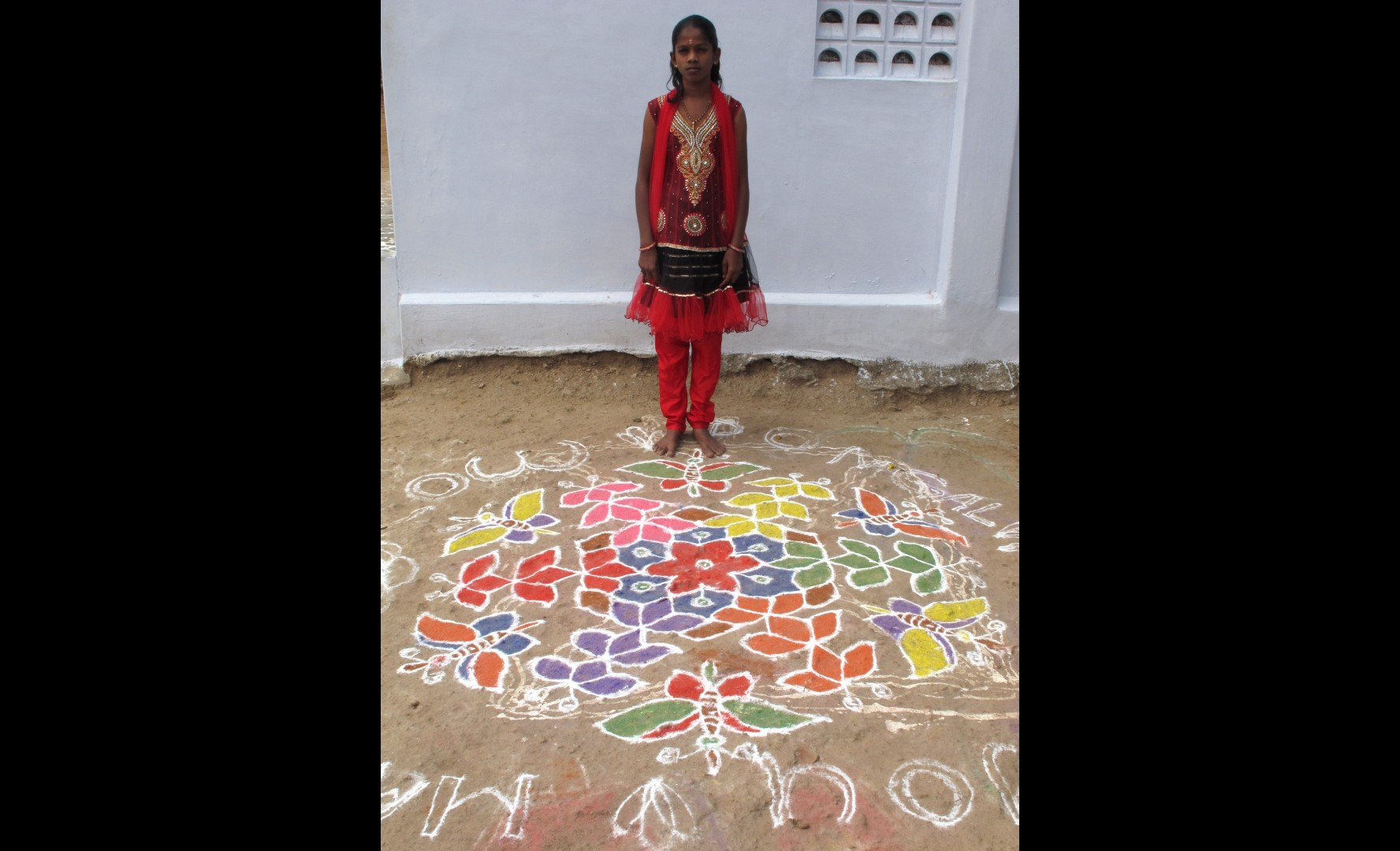 Sukkanya poses with the kolam she and her sister traced that morning